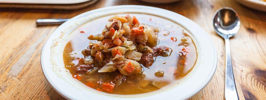 Un piatto pieno di tipica zuppa di agnello. Sulla destra, un cucchiaio.