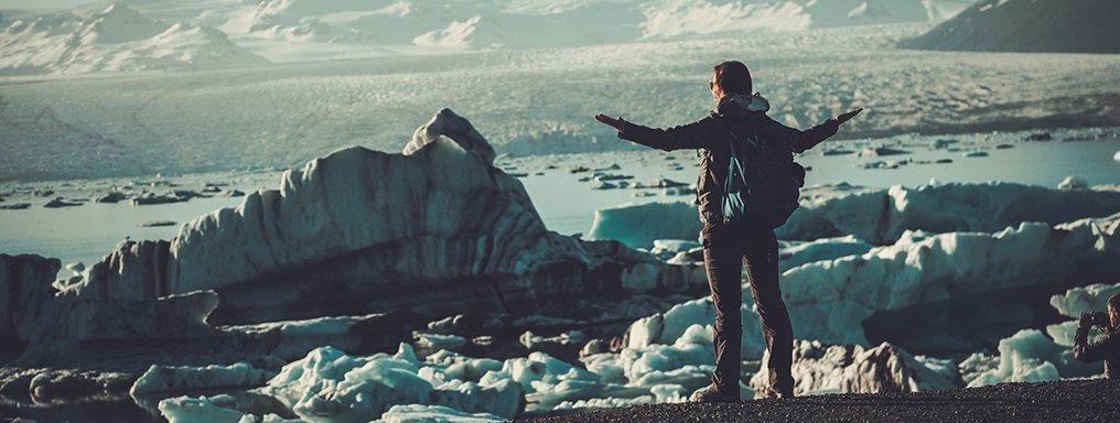 Una persona spalanca le braccia di fronte a una laguna glaciale piena di iceberg