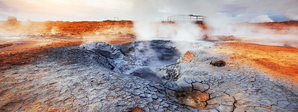 Fumarole e pozze di fango che ribolle. La terra è grigia e rossa, l'aria satura di vapore.