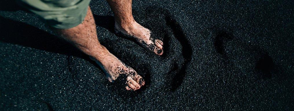 I piedi nudi di una persona appoggiano sulla sabbia nera.